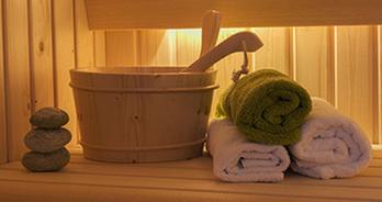 Stenen, een emmer en handdoeken in een sauna